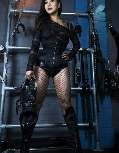 Dominant strong alpha female holding BDSM equipment